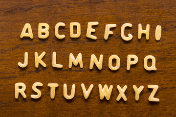 Alphabet made of macaroni letters isolated on wood background