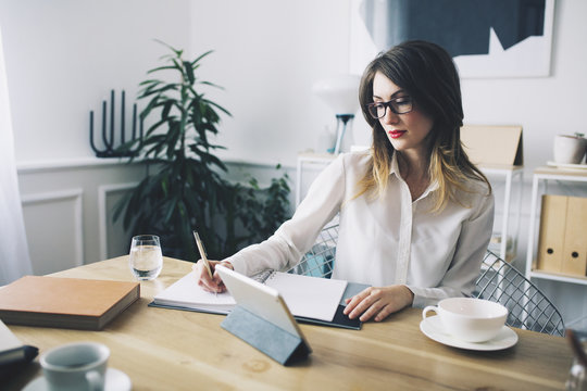 Businesswoman writing while sitting at desk in office