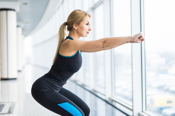 Side view of young woman in sportswear doing squat and holding dumbbells while standing in front of window at gym