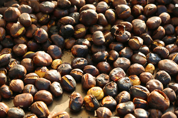 many roasted chestnuts for sale in the stall in the street