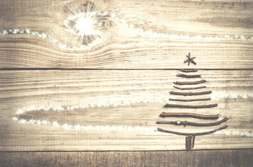 Christmas tree arranged from sticks on wooden sparkly grey background.