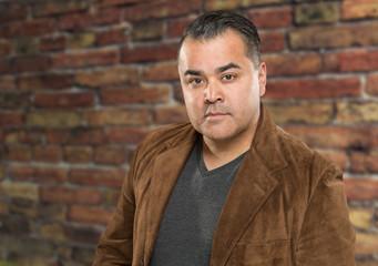 Handsome Young Hispanic Male Headshot Portrait Against Brick Wall.
