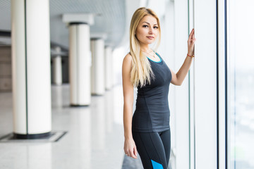 Young woman near big panaramic windows in sport wear before treaining,