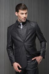 Man model in dark grey waistcoat, trousers, shirt and cravat