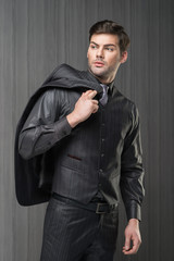 Man model in black waistcoat, trousers, shirt and cravat holding jacket