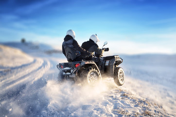 Foto auf Acrylglas Motorsport Quad bike in motion, ride on top of the mountain on snow. People riding quad bike on mountain at sunset