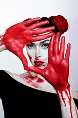 Beauty style portrait of a girl in a high fashion with close eyes, beauty style with white skin, red lips make up at silver background. Vampire makeup Fashion Art design. Halloween holiday concept