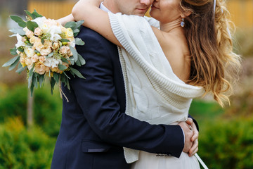 Bride embracing groom and holding a bouquet