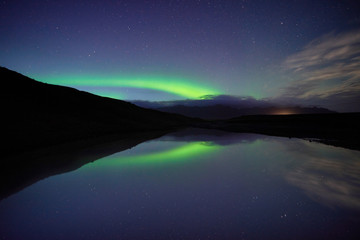 Reflections of aurora borealis over the jokulsarlon lagoon, iceland. image noise due high ISO