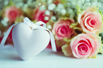 Decorative heart with a bouquet of roses on a wooden table