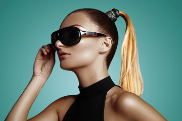 Beautiful young woman with black fashion sunglasses and glamour pinytail hairstyle. Eye wear style