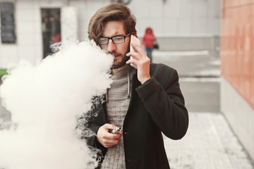 Young hipster man with a beard and glasses smokes an electronic cigarette. He says on his cell phone. Youth fashion. Delicious pairs. A cloud of steam.