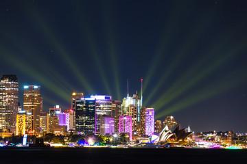 Sydney cityscape at night with colorful lights illuminating skyline