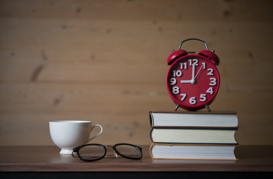 Alarm clock at 9am on stack of books with glasses and a cup of coffee on wooden table. Education concept.