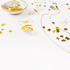 Beauty blog background. Gold style feminine accessories. Golden tinsel, pen, rings on white background. Top view.
