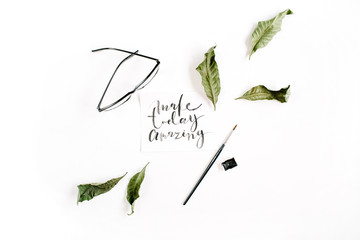 """Inspirational quote """"Make Today Amazing"""" written in calligraphic style on paper with green leaf and glasses on white background. Flat lay, top view"""