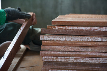 man working on the  wood  coarse sand paper.