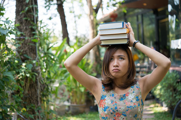 Happy charming young woman standing and holding notebooks at home garden. Education concept.
