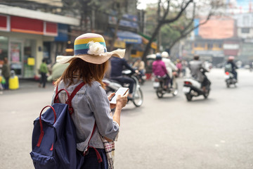 Young traveller using an app on her smartphone