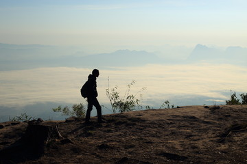 Man walking on the cliffs and mist at Phu Kradung National Park,Thailand