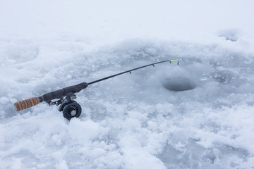 Ice fishing rod on frozen lake covered with snow