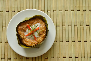 steamed fish with curry paste stuffed Indian mulberry in coconut cream on banana leaf cup