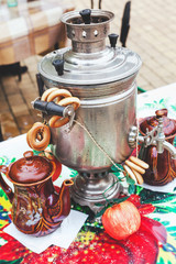 Samovar, bagels and tea on bright tablecloth on holiday carnival