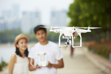 young asian couple operating a drone, focus on the drone Wall mural