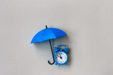 Blue alarm clock under an umbrella