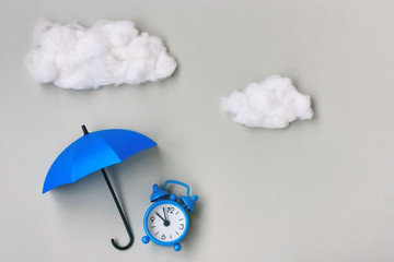 Blue alarm clock under an umbrella on gray background