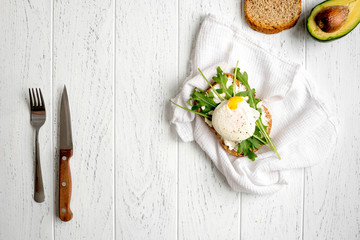 sandwich with poached eggs on wooden background top view