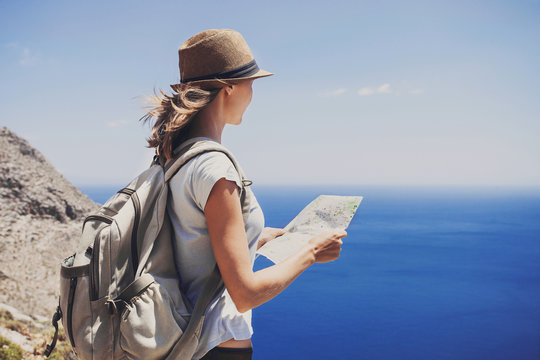 Back side of traveler girl standing with map and looking at the sea, travel, hiking and active lifestyle concept