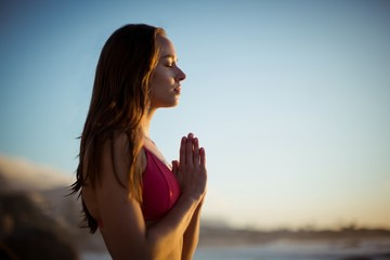 Beautiful woman meditating on beach
