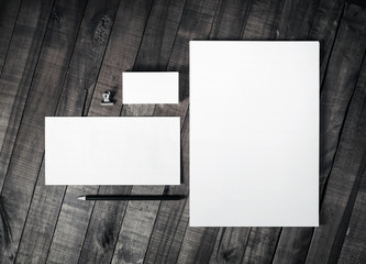 Photo of blank corporate identity. Branding mockup. Sheets of paper, letterhead, business cards, envelope and pencil on wooden table background. Blank stationery set. Mock up for ID. Top view.