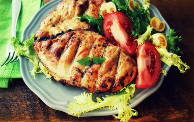 Grilled chicken breast on wooden background