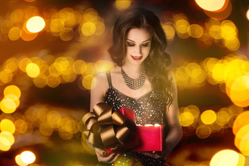 Surprised woman is opening red gift box bokeh background