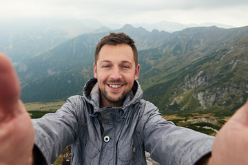 Smiling hiker taking a selfie in front of mountain landscape Wall mural