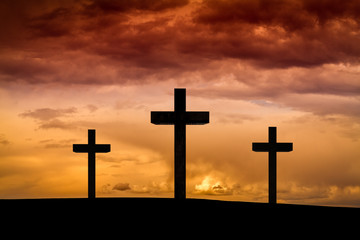 Jesus Christ cross in Easter Friday evening on red, orange sky with dramatic clouds,dark sunset. Three wood crosses on Golgota Mountain. Calvary, Easter,Crucifixion, resurrection, Good Friday concept