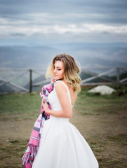 Bride in perfect white dress with open back poses on hill in cloudy day