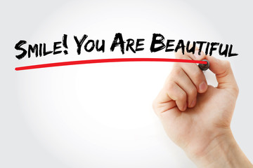 Hand writing Smile! You Are Beautiful with marker, concept background