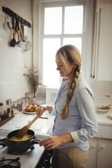 Woman preparing noodles in kitchen
