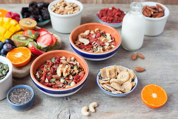 Paleo style nut cereal with fruits and berries on the wooden table, selective focus