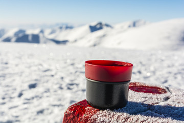 Hot tea in a cup from a thermos on the table with a boundary marker.