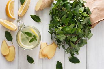 Detox lemonade smoothie ingredients on white wood background, top view