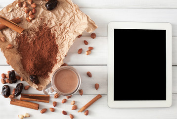 Chocolate smoothie ingredients on white wood with tablet screen