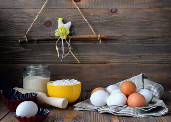 Fresh chicken eggs kitchen wooden table for making a festive Easter cake, dark background