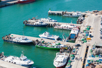 Port of Barcelona. Fishing boats scattered on the dock fishing nets