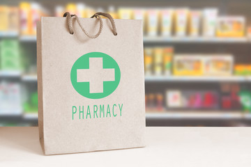 Recycled paper bag with a green Pharmacy logo in a drugstore. Empty copy space for Editor's content.