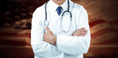 Composite image of doctor standing with arms crossed