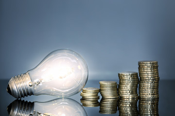 Leuchtende Glühbirne und Kleingeld